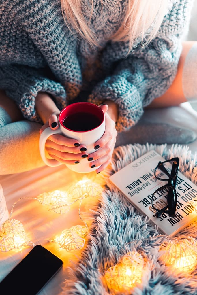 Woman in grey sweater holding a cup of tea with a book on how to better herself on grey furry carpet