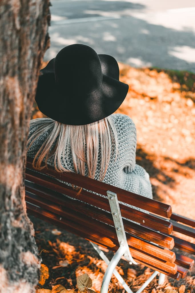 Blonde haired woman sitting on a bench backview contemplating