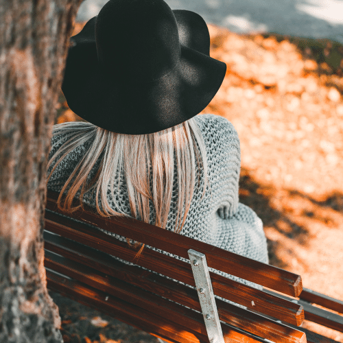 woman-sitting-on-bench-wearing-a-black-hat