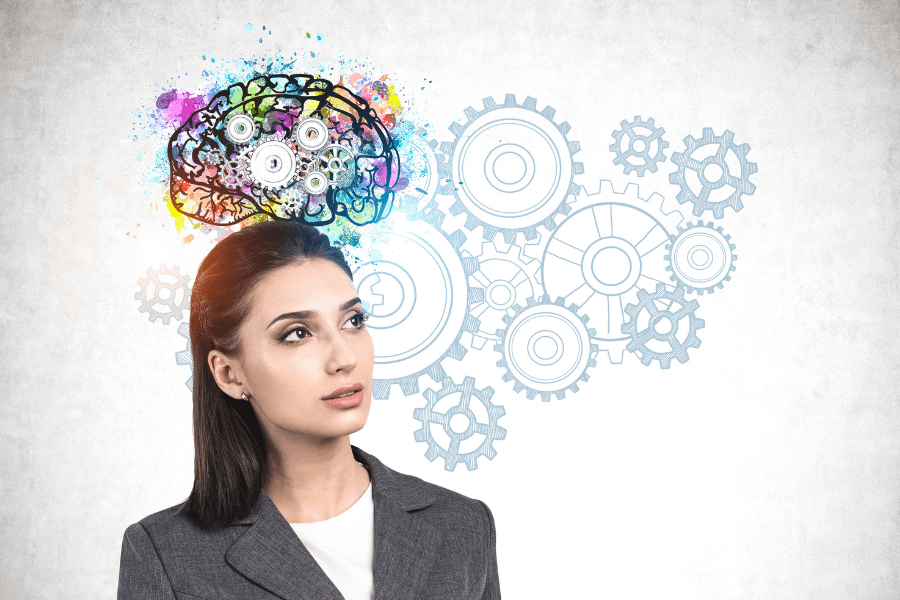 Young dark-haired businesswoman standing near a concrete wall with colorful brain sketch representing cognitive distortions