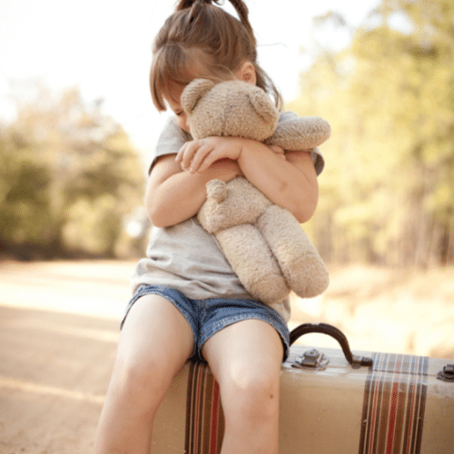 little-girl-with-teddy-bear-sitting-on-suitcase-by-the-raodside