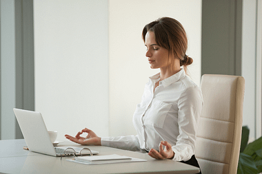 Woman practicing mindfulness at her desk using compassion and understanding.